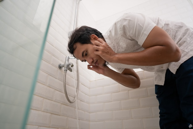 Мужчина-мусульманин перед молитвой очищает свое тело водой из-под крана. омовение омовение чистка