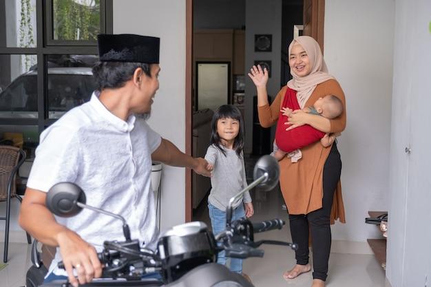 Мусульманский мужчина едет на мотоциклетном скутере, оставив свою семью дома