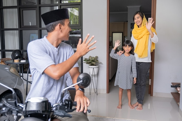 Muslim man going by motorcycle scooter leaving his family behind at home asian family travelling
