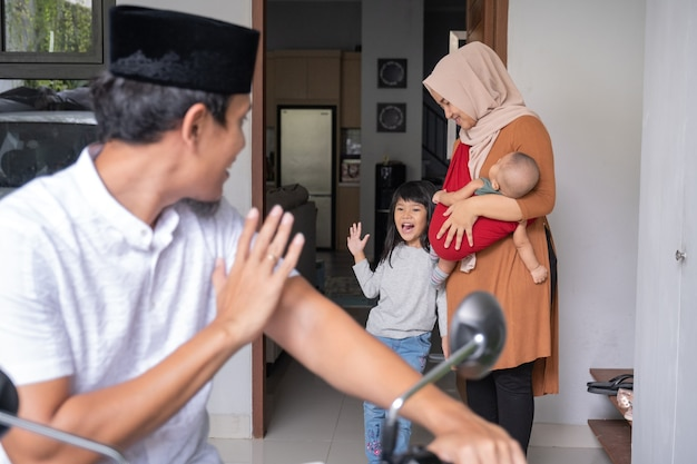 Muslim man going by motorcycle scooter leaving his family behind at home