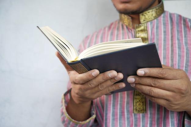 Мусульманин рука читает священную книгу коран с копией пространства