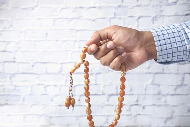 Мусульманин рука с четками молится крупным планом