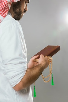 Muslim man holding quran and praying bead