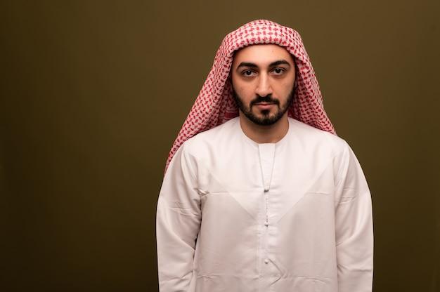 Мужчина-мусульманин в хиджабе. портрет молодого арабского человека в традиционной одежде. фото высокого качества