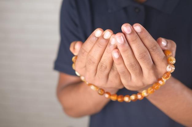イスラム教徒の男性は、ラマダンのクローズアップ中に祈りのジェスチャーで手を保ちます