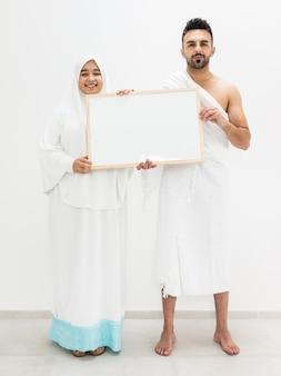 ホワイトボードを持ってメッカでkaabaを訪問するhajjの準備としてポーズをとっているイスラム教徒の男