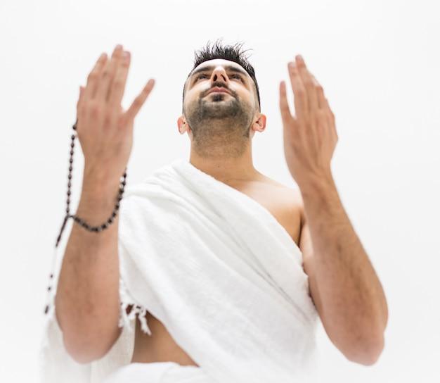 メッカのkaabaを訪問するhajjの準備としてポーズをとっているイスラム教徒の男
