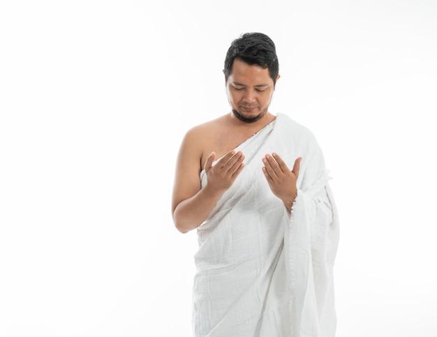 Мусульманин молится в белой традиционной одежде
