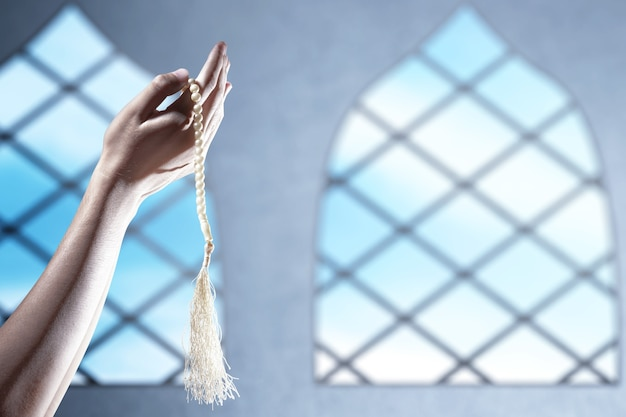 Muslim man praying with prayer beads on his hands on the mosque