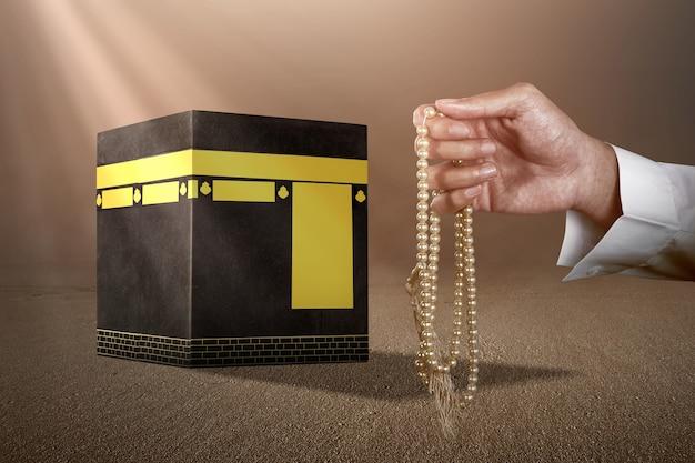 日光の背景でカーバ神殿の前で彼の手に数珠で祈るイスラム教徒の男性