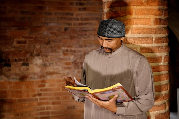 Muslim man reading the qur'an at an old mosque in ayutthaya province, thailand.