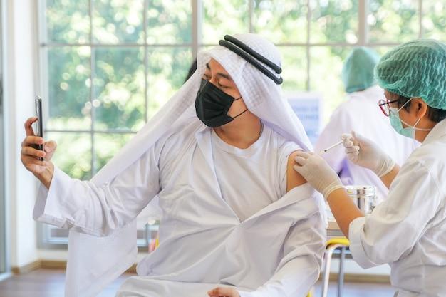 코비드 백신 간호사가 손 덮개 석고 팔을 사용한 후 전화로 이슬람 남자 셀카
