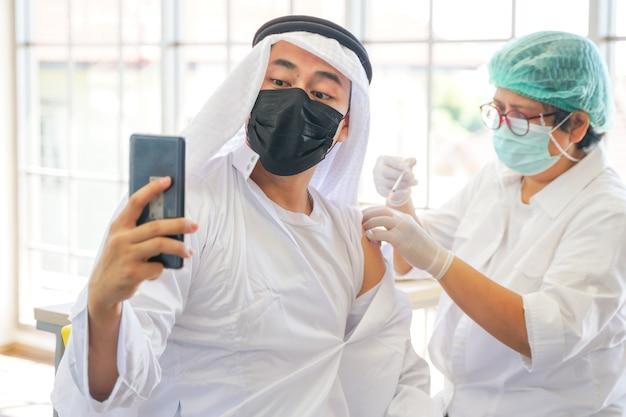 コロナワクチンを接種した後の電話でのイスラム教徒の男性の自撮り看護師はハンドカバーの石膏アームを使用します