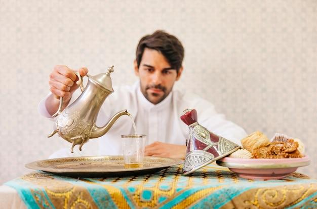 Мусульманский человек, сидящий на столе с чаем