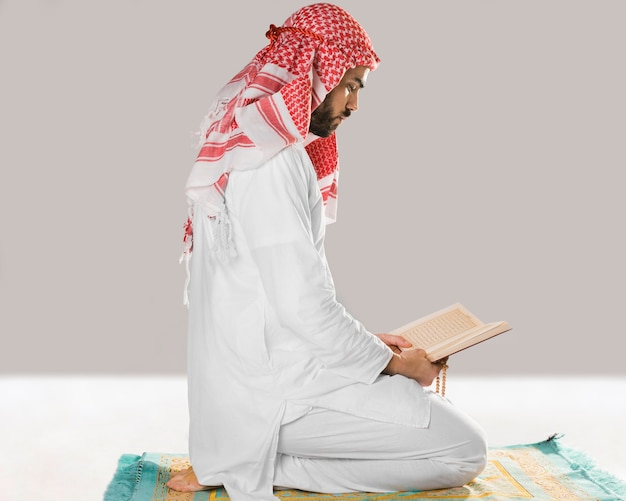 Muslim man sitting and reading from quran