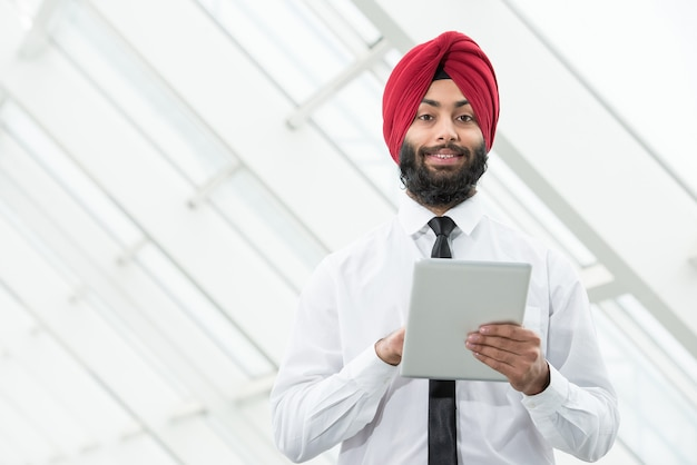 Muslim man stands with a tablet and looks at something.