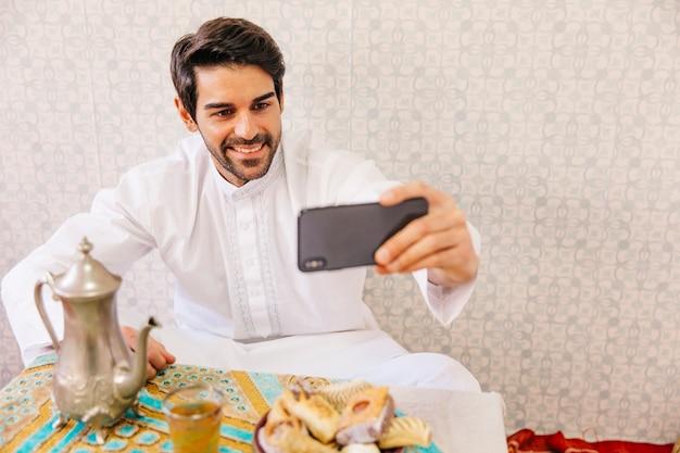 Uomo musulmano prendendo selfie