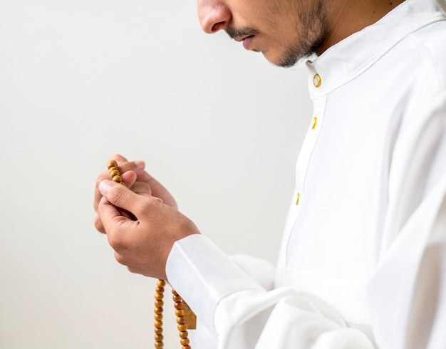 Muslim man using misbaha to keep track of counting in tasbih