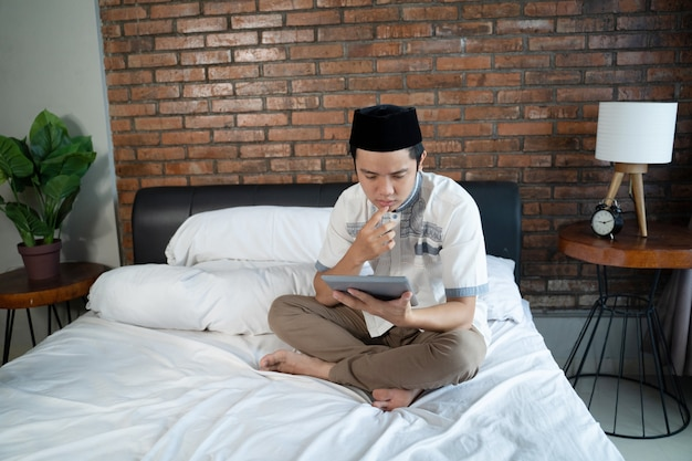 Muslim man wearing cap using tablet sitting on bed