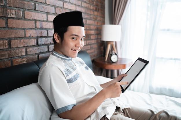 침대에 앉아 태블릿을 사용하여 모자를 쓰고 이슬람 남자