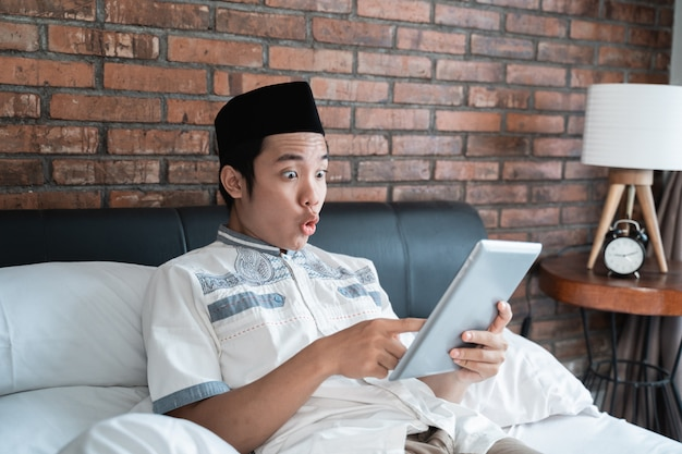 Muslim man wearing cap using tablet with surprised expression