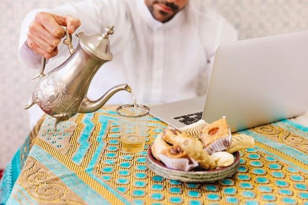 Uomo musulmano con cibo e laptop