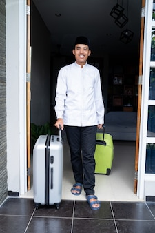 Muslim man with head cap holding suitcase