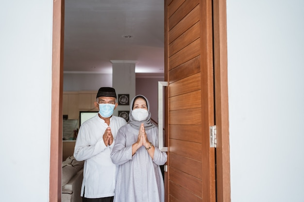 Muslim mature couple wearing face mask standing at front door of their house with greeting gesture