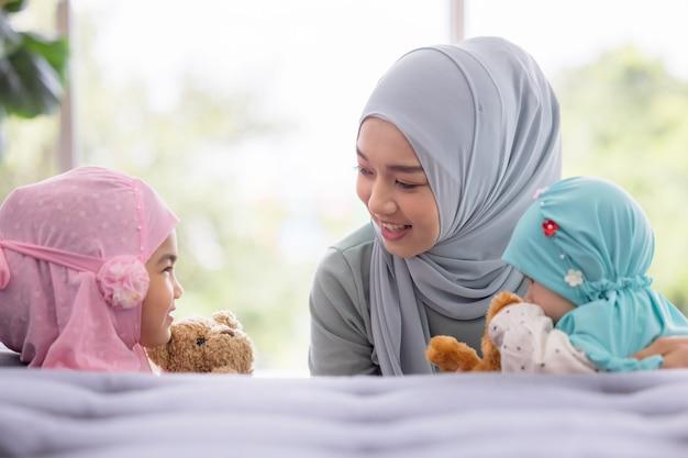 ヒジャーブのイスラム教徒のお母さんは、リビングルームに座っている彼女の小さな娘、愛情のある関係です