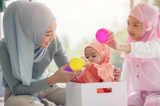 히잡의 무슬림 엄마는 거실에 앉아있는 작은 딸, 사랑의 관계입니다.