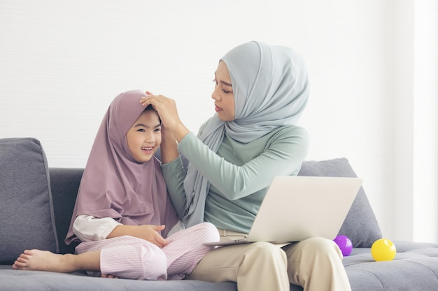 Hijab의 무슬림 엄마는 거실에 컴퓨터가 앉아있는 어린 딸입니다. 사랑하는 관계