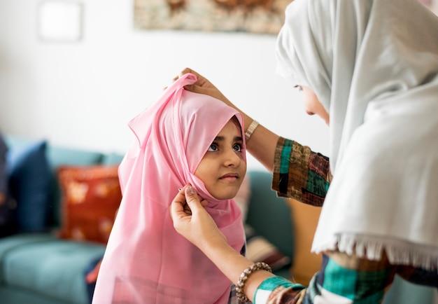 ヒジャーブの着用方法を娘に教えるイスラム教徒のお母さん