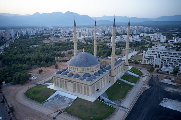 トルコ、アンタルヤのイスラム教モスク。青いモスクミナレットと山々を背景にした街のスカイラインの上面図。