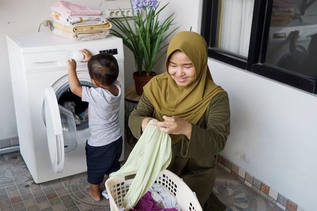 イスラム教徒の母親、赤ちゃんと一緒に洗濯機で洗濯をしている主婦