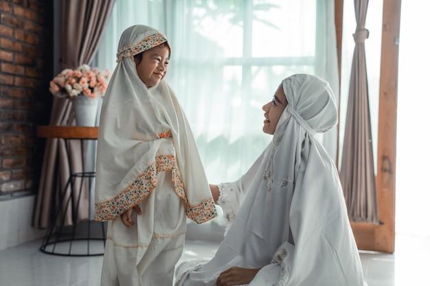 祈るスカーフを持つイスラム教徒の母と子