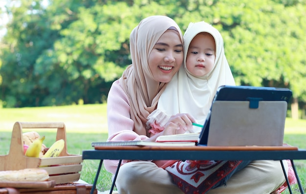 イスラム教徒の母と娘は公園でリラックスして楽しんでいます。