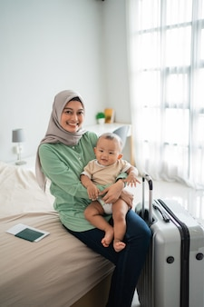 Muslim mother carry her baby while sitting on the bed