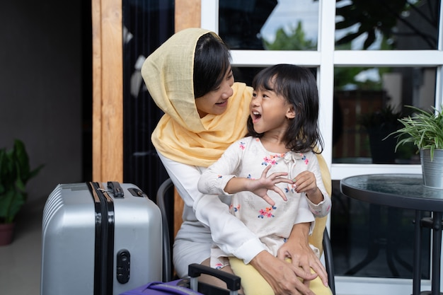 Muslim mother and daughter with suitcase