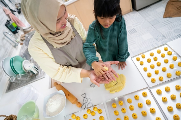Muslim mother during ramadan activity with her daughter making a nastar cake together