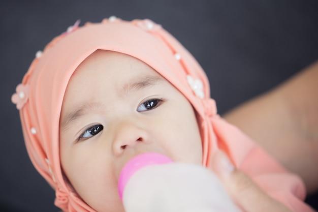 イスラム教徒の母親が赤ちゃんに牛乳瓶を与えています。