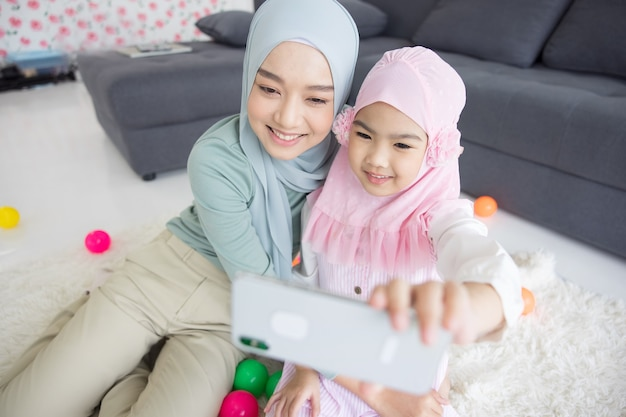 Muslim mother future motherhood in hijab and taking self portrait in living room