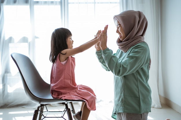 Muslim mother highfive with daughter