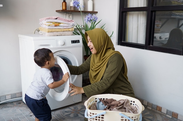 Muslim mother a housewife with a baby engaged in laundry with washing machine