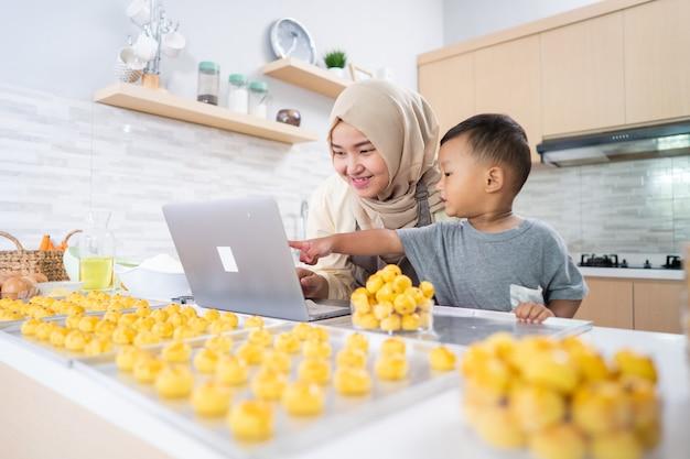 부엌에서 그녀의 아들과 함께 케이크를 만드는 동안 노트북을보고 이슬람 어머니. 나 스타 케이크