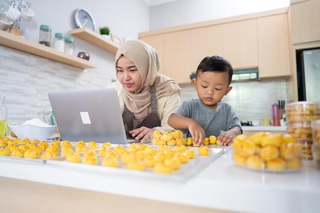 Мусульманская мать смотрит на ноутбук, делая торт с сыном на кухне. настарь торт