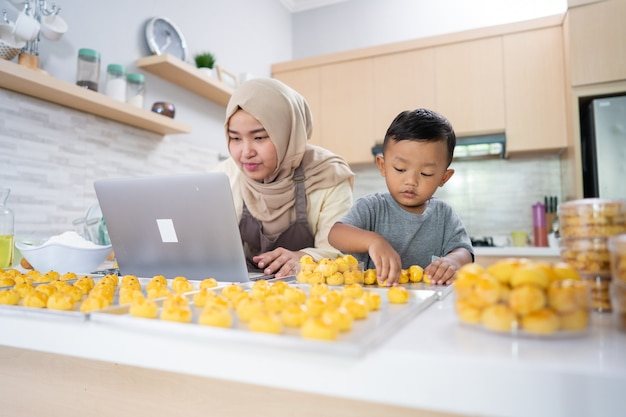 Muslim mother looking at laptop while making cake with her son in the kitchen. nastar cake