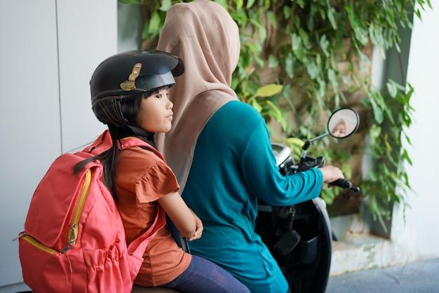 Мать-мусульманка забирает дочь в школу утром на мотоцикле. азиатская ученица начальной школы снова в школе