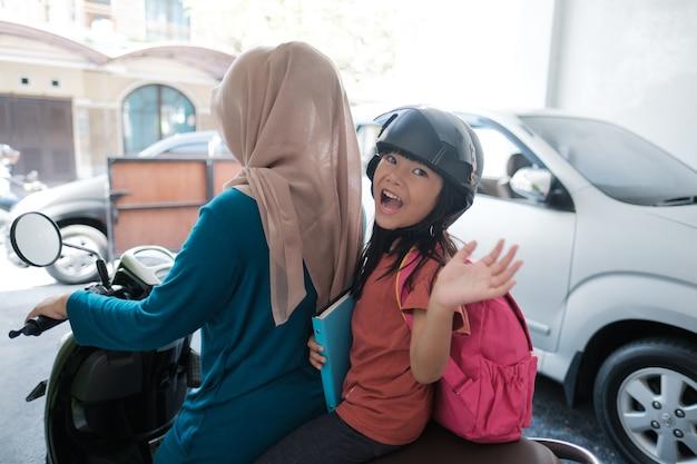 Мать-мусульманка забирает дочь в школу на мотоцикле утром
