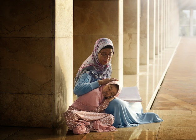 Muslim mother teach her daughter reading koran