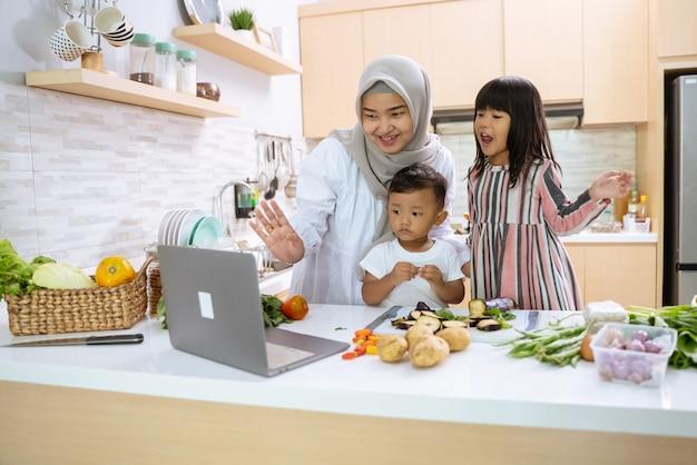 Мать-мусульманка смотрит видео о приготовлении пищи на ноутбуке и вместе с двумя детьми готовит ужин на кухне